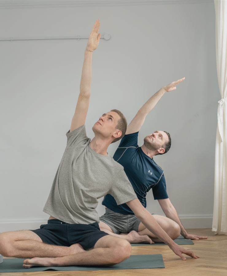 men in sitting yoga pose stretching arm over head